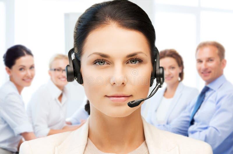 Operador del servicio de ayuda con los auriculares en centro de llamada imagenes de archivo