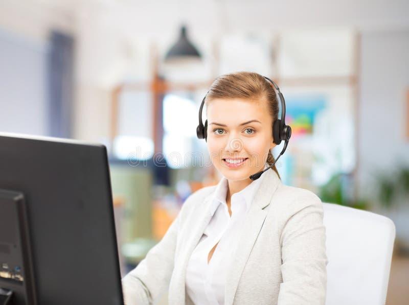 Operador del servicio de ayuda en el funcionamiento de las auriculares en la oficina imágenes de archivo libres de regalías