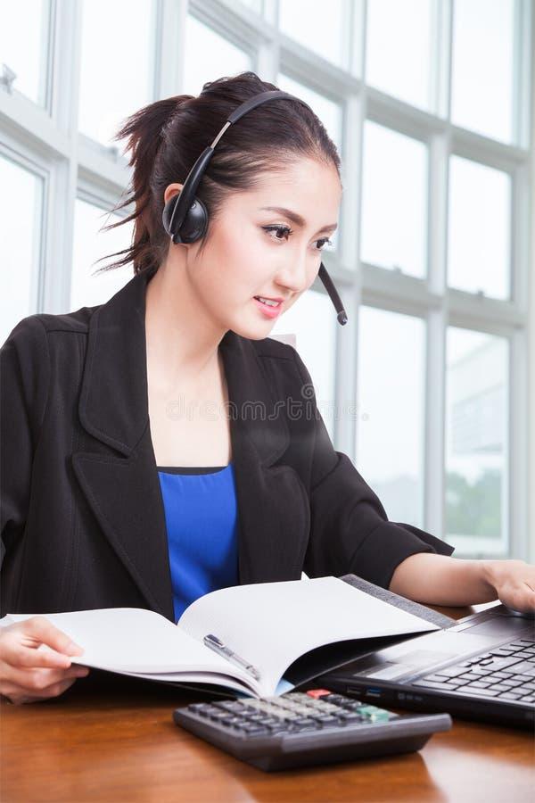 Operador fêmea asiático amigável da linha aberta com fones de ouvido imagem de stock royalty free