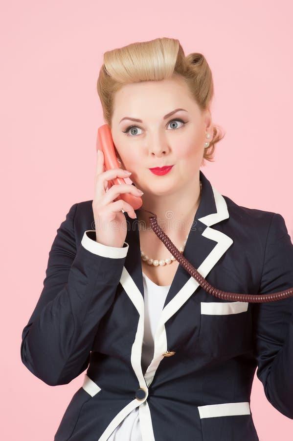 Operador fêmea louro com bordos vermelhos que chama sobre o telefone de orador vermelho do receptor A mulher atrativa com ondas l fotografia de stock royalty free