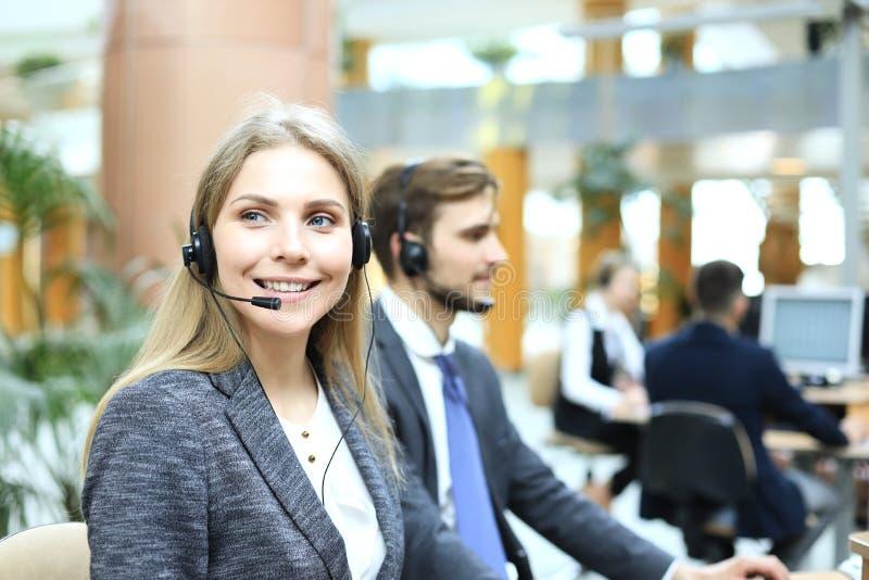 Operador f?mea do apoio ao cliente com auriculares e sorriso fotografia de stock