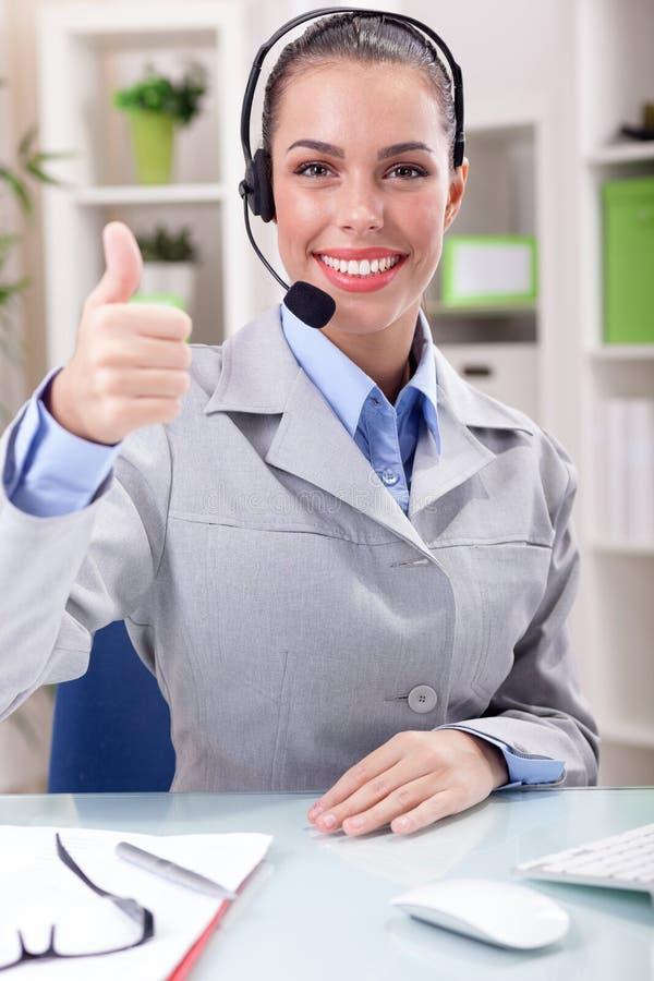 Operador hermoso del teléfono de la ayuda en auriculares en el lugar de trabajo fotos de archivo