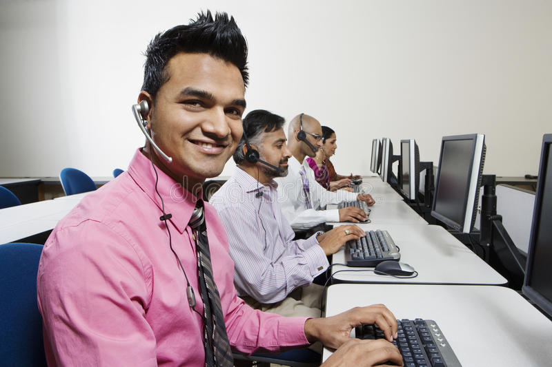 Operador joven del servicio de atención al cliente con los colegas en la oficina fotos de archivo