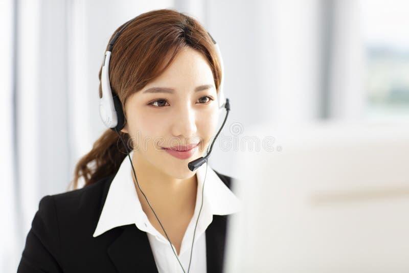 Operador joven hermoso de la mujer de negocios en auriculares foto de archivo libre de regalías