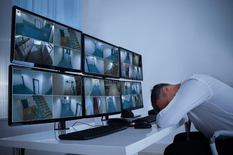 Operador masculino que dorme na segurança Monitor& x27; mesa de s imagem de stock