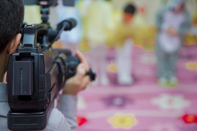 Operador profissional que trabalha com seu equipamento, fundo borrado da câmara de vídeo Operador da câmara de vídeo que trabalha fotografia de stock