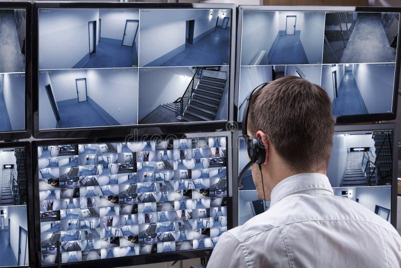 Operador que olha a metragem múltipla da câmera no computador imagens de stock