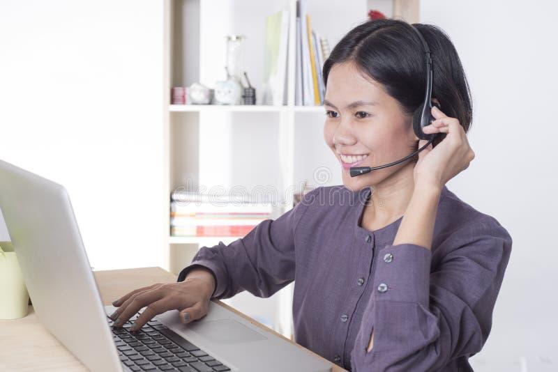 Operador sonriente feliz de la atención al cliente de las mujeres de Asia con las auriculares foto de archivo