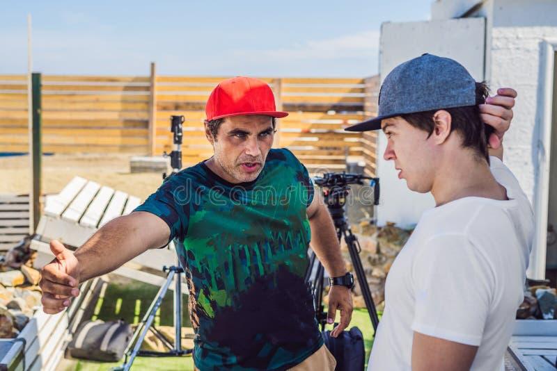Operador y director de la cámara discutir el proceso de un lanzamiento video comercial foto de archivo libre de regalías