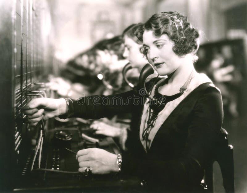 Operadores de centralita telefónica en el trabajo imagen de archivo libre de regalías
