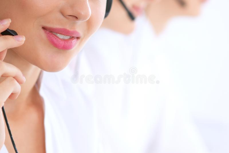 Operadores de centro de atención telefónica desconocidos en el trabajo Foco en los labios hermosos de la mujer imagen de archivo libre de regalías