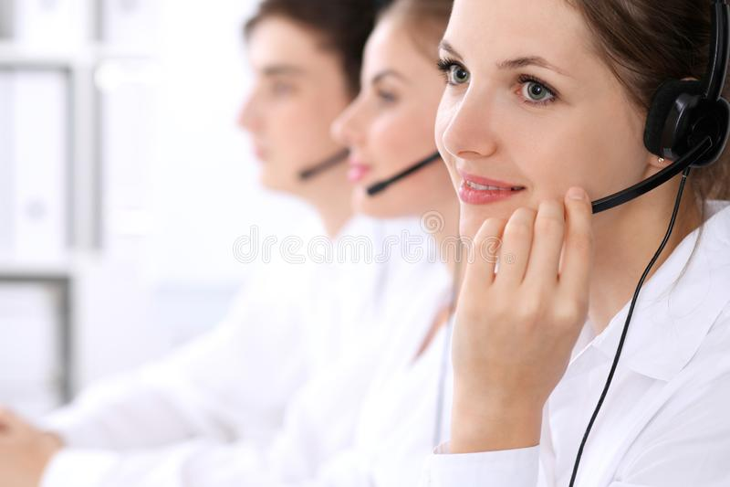 Operadores de centro de atendimento Foco na mulher bonita nos auriculares fotografia de stock royalty free