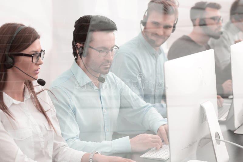 Operadores de la ayuda en el lugar de trabajo en el centro de atención telefónica imagen de archivo