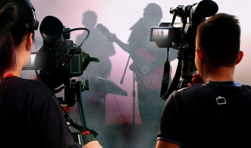 Operadores de la cámara que trabajan con el equipo de vídeo en el concierto fotos de archivo libres de regalías
