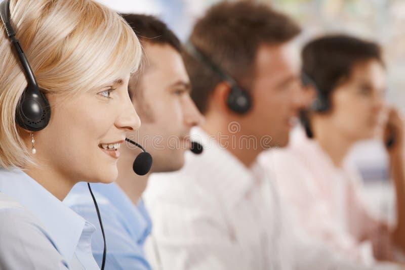 Operadores do serviço de atenção a o cliente em uma fileira fotos de stock