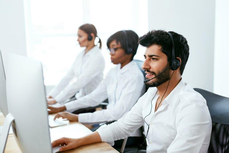 Operadores que trabajan en la línea directa en centro de atención telefónica foto de archivo libre de regalías