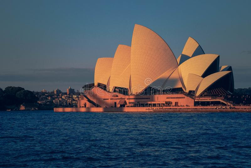 Operahus under solnedgånganseende i blå havkust och himmellinje i Sydney på en sommardag arkivbild
