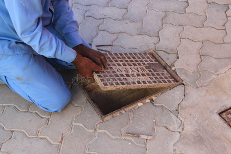 Operai che aprono una botola per riparare una perdita dell'acqua fotografia stock