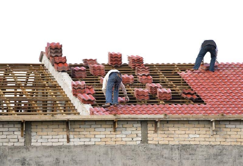 Operai che pongono le mattonelle di tetto fotografia stock libera da diritti