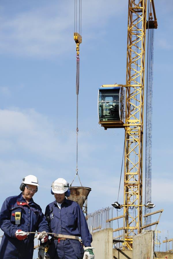 Operai e gru della costruzione nell'azione immagine stock