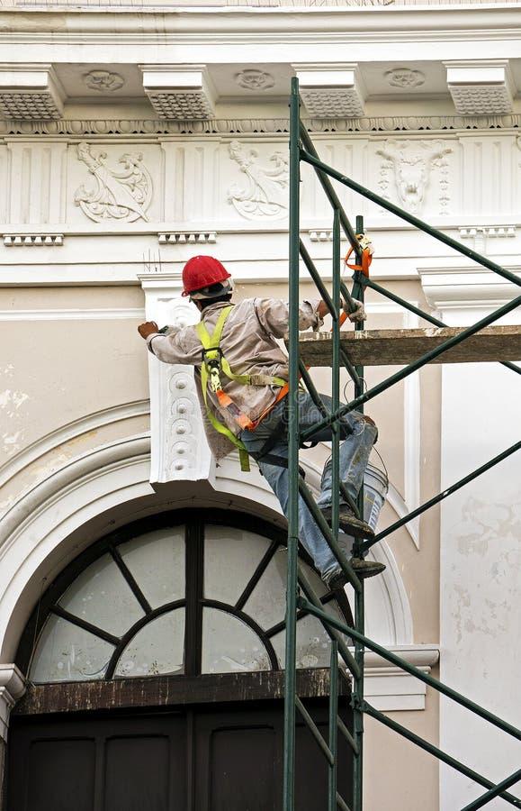 Operaio che dipinge una facciata della costruzione da un'impalcatura fotografia stock