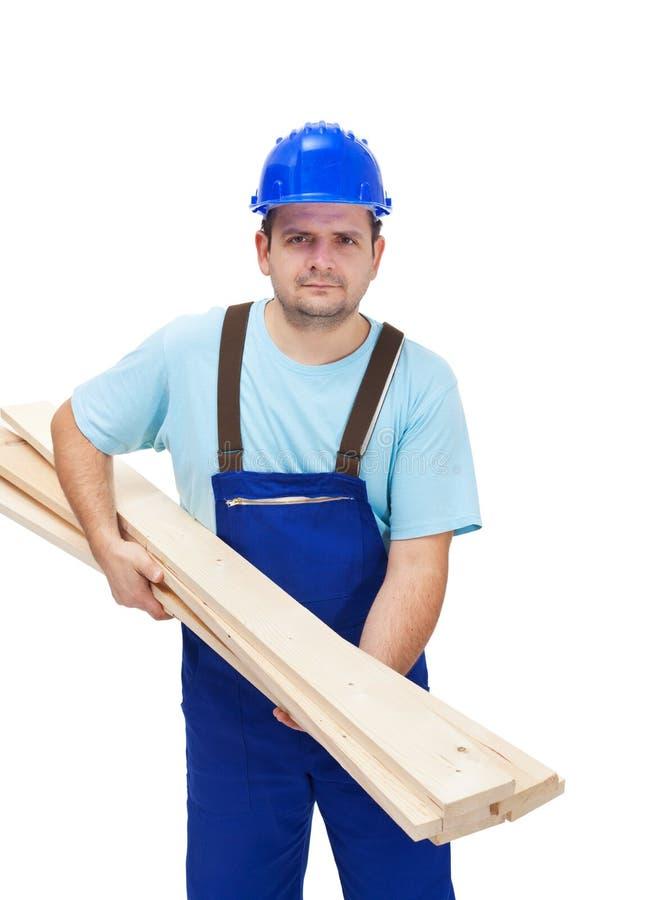 Operaio che trasporta i plancks di legno immagini stock