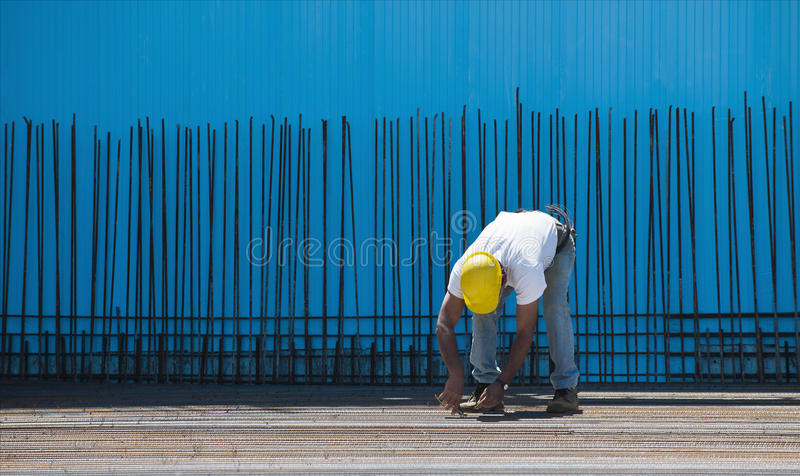 Operaio di costruzione che installa i collegare obbligatori fotografia stock