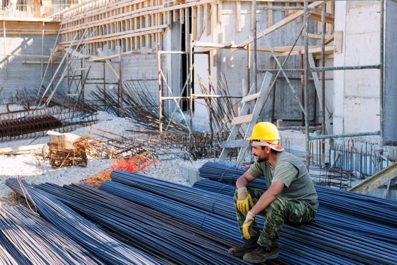 Operaio di costruzione che riposa sulle barre d'acciaio immagine stock