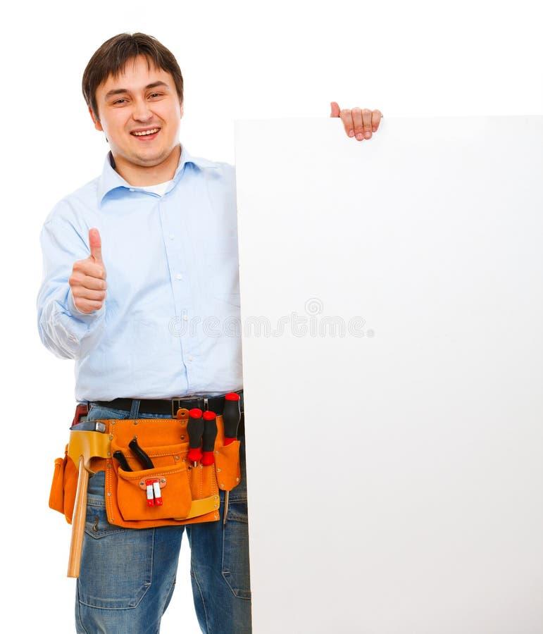Operaio di costruzione che tiene tabellone per le affissioni in bianco immagine stock