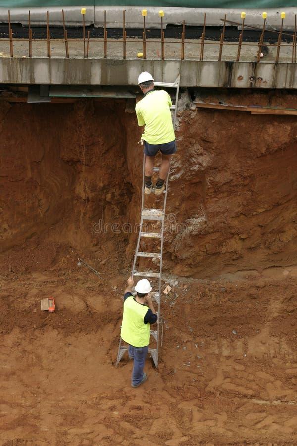 Operaio di costruzione su una scaletta immagine stock