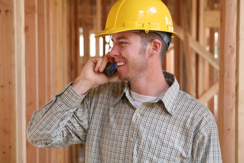 Operaio di costruzione sul telefono immagine stock