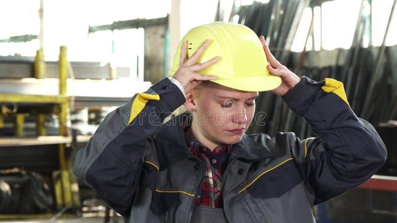 Operaio femminile stanco che decolla il suo elmetto protettivo dopo il lavoro fotografia stock libera da diritti