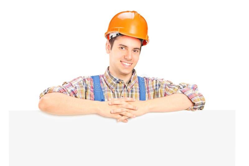 Operaio maschio soddisfatto che si leva in piedi dietro il comitato immagini stock
