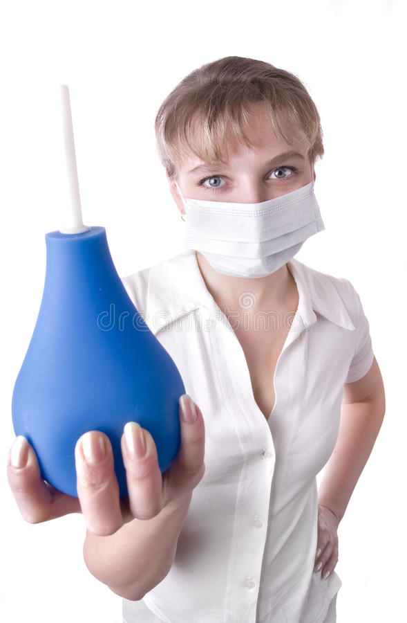 Operaio medico che tiene un enema blu in sue mani immagine stock libera da diritti