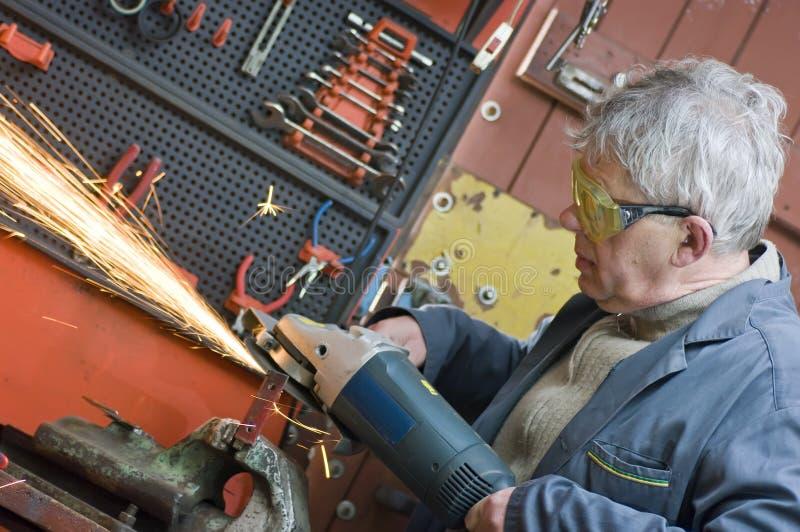 operaio metallurgico e sega elettrica fotografia stock libera da diritti