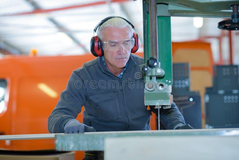 Operaio metallurgico senior che fa funzionare la fresatrice di CNC fotografie stock
