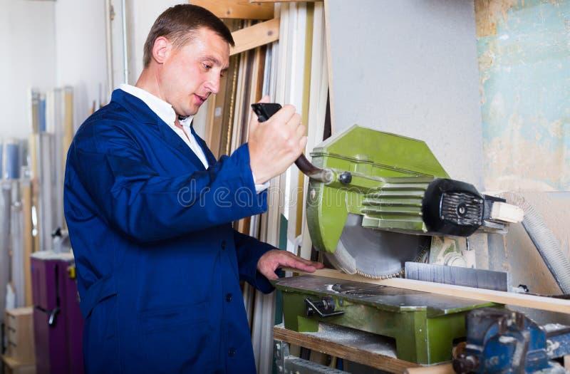 Operaio professionista che taglia le plance di legno facendo uso della sega circolare fotografia stock libera da diritti