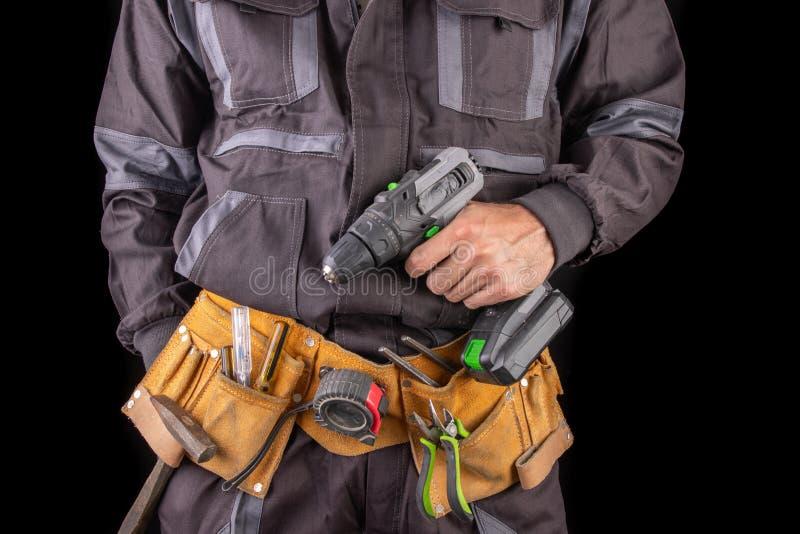 Operaio in vestiti da lavoro e cinghia dello strumento Addetto alla produzione con un trapano dentro la sua mano immagini stock libere da diritti