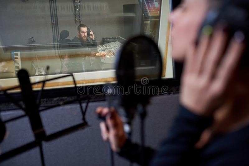 Operatör som arbetar med sångaren i studio royaltyfria foton