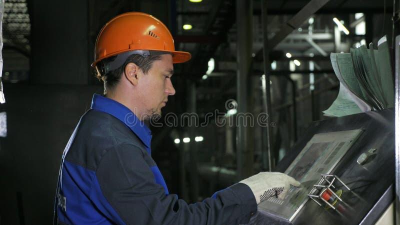 Operatören övervakar kontrollbordet av produktionslinjen Tillverkning av den plast- fabriken för vattenrör Process av danande royaltyfria bilder