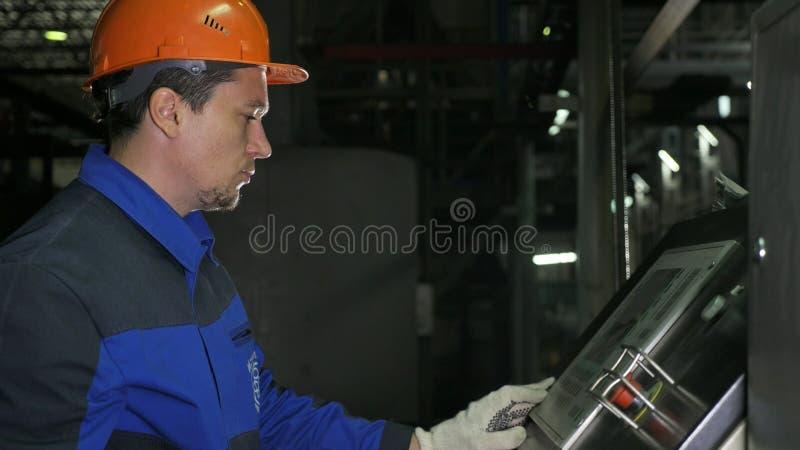 Operatören övervakar kontrollbordet av produktionslinjen Tillverkning av den plast- fabriken för vattenrör Process av danande royaltyfri fotografi