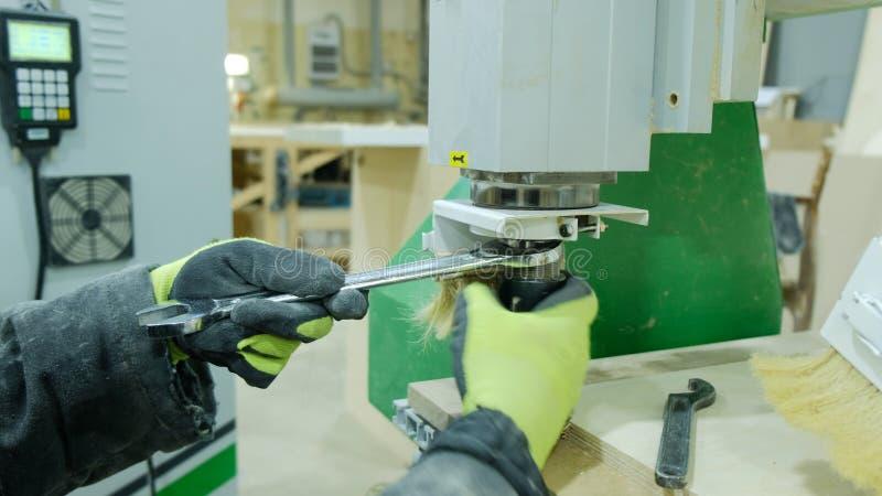Operatören av en modern CNC-snickerimaskin gör justeringar för arbete Ändrar skäraren med tangenterna och nollställningarna arkivfoton