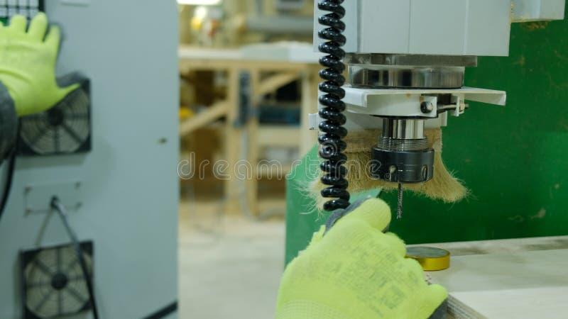 Operatören av en modern CNC-snickerimaskin gör justeringar för arbete Ändrar skäraren med tangenterna och nollställningarna royaltyfri fotografi