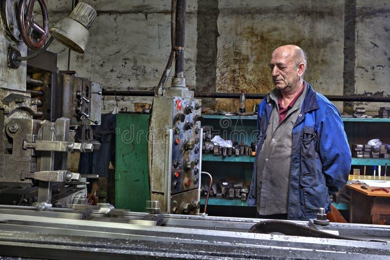 Operatören för maskinhjälpmedlet, tråkig malning för hyvlare kontrollerar processin royaltyfri foto