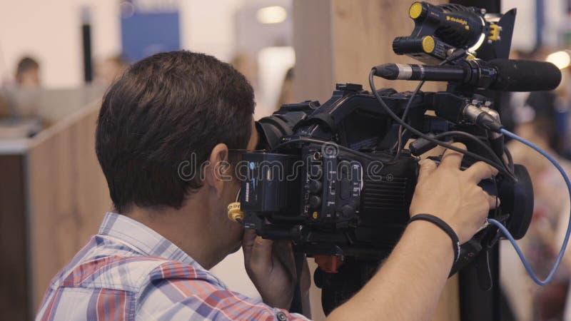 Operatören tar bort en rapport på den yrkesmässiga kameran Operatören tar bort kameran royaltyfri bild