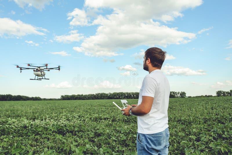 Operating молодого человека octocopter трутня летания на зеленом поле стоковое изображение rf
