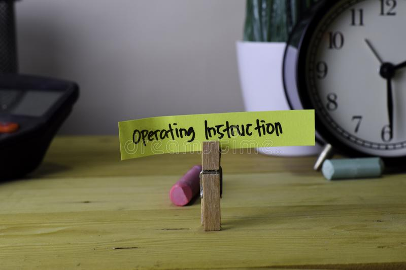 Operating Instruction. Handwriting on sticky notes in clothes pegs on wooden office desk stock photography