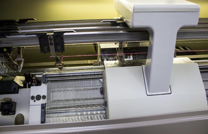 Operating a Knitting machine at the factory. The management of a modern knitting machine in the factory royalty free stock images