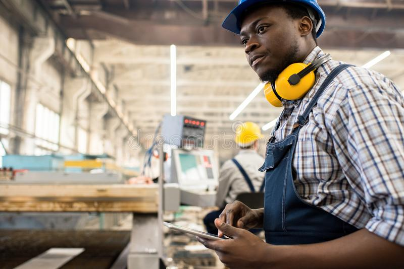 Operating Machine with Digital Tablet. Concentrated African American worker wearing overall and hardhat operating machine with help of digital tablet, interior stock image