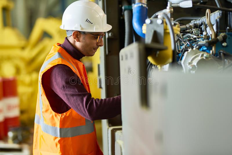 Operating Machine at Production Department. Profile view of mixed-race worker wearing reflective vest and protective helmet operating machine while standing at royalty free stock images